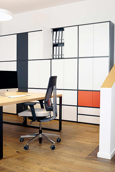 """Symple"" design desks with a shelf unit in black and white and a coloured accentuation"