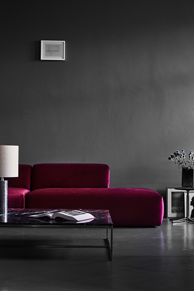 Sofa in red velvet combined with a black marble side table