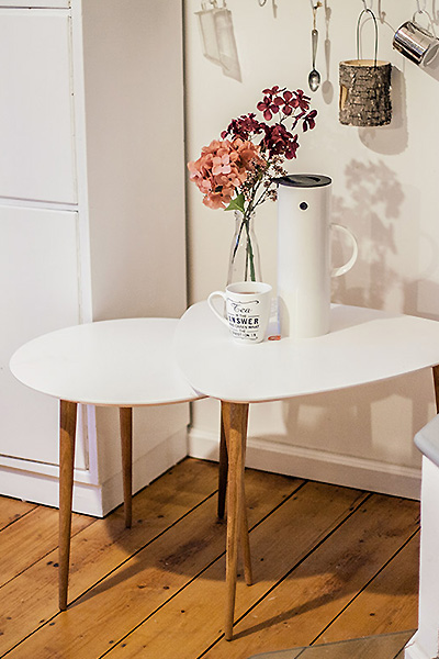 One round and one triangular side table with legs in oak and tabletop in white